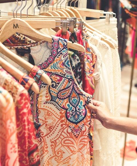 En kvinna som väljer bland kläder