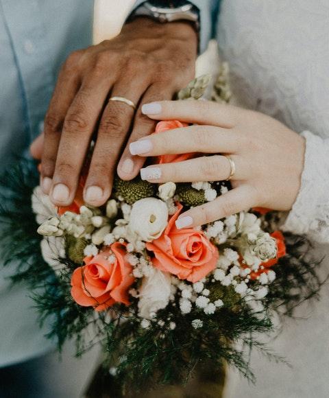 Händer med vigselringar och en brudbukett